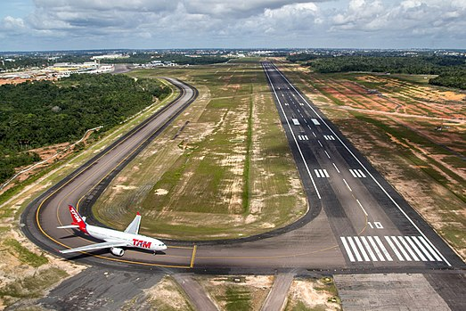 View of Eduardo Gomes International Airport's runway 10 (with TAM Airlines Airbus A330-200 holding short). Manaus city center is at the background. PistaaeroportodeManaus.jpg