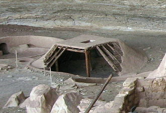 Pit-house - A reconstruction of a pit-house at the Step House ruins in Mesa Verde National Park, United States, shows the pit dug below grade, four supporting posts, roof structure as a layers of wood and mud, and the entry through the roof.