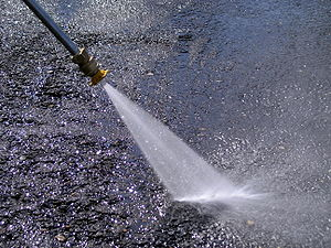 Pressure washing - A pressure washer cleaning oil-clogged tarmac