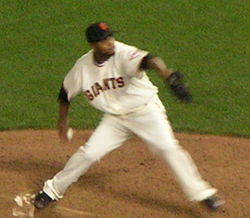 Ramírez in a white uniform that says Giants in black letters preparing to throw a pitch