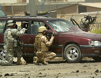 Battle of Ramadi (2006) - US troops take cover from small arms fire while investigating a car bomb explosion in Tameem, Ramadi, August 10, 2006.
