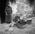 Razne posode pred hišo in zraven gospodinja, pr' Jerišeta, Socerb 1949.jpg