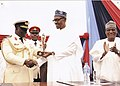Rear Admiral Samuel Ilesanmi Alade, then the Commandant National Defence College Nigeria, presenting a token trophy to The President of the Federal Republic of Nigeria, HE Mohammadu Buhari at the College Graduation Ceremony in 2016.jpg