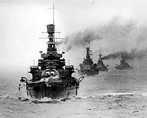 A formidable line of warships with big guns heads straight toward you, trailing smoke