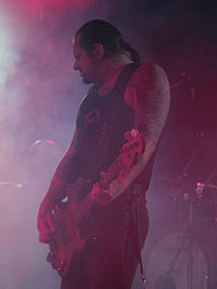 Man shown in left profile, he is playing a guitar, facing his right. Long hair tied at back, arms are tattooed.