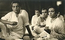 Photograph of Satyajit Ray seated with Ravi Shankar with several others in the background