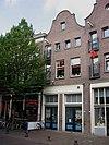 foto van Pand met klokgevel met tussendekplaten, oorspronkelijk pakhuis. Onder een dak met het nr 21