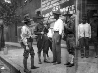 Washington race riot of 1919 - Three armed European-Americans questioning an unarmed African-American on the pavement