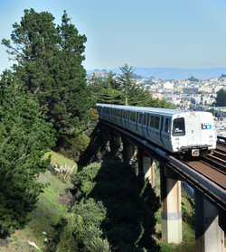 A southbound BART train passes San Francisco's Outer Mission neighborhood, between the Balboa Park station and the Daly City station. The photograph was taken on the pedestrian bridge next to the San Jose/Farallones stop of the SFMTA M line.