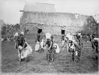 Taukei ni Waluvu - Meke Wesi- Spear Dance, Nakorovatu, Matailobau 1881. A group of traditionally dressed Matailobau warriors with charcoal blackened faces in three lines grasping their spears and leaning forward on their war clubs. Most are wearing turban like head gear. Behind them are densely thatched village buildings, and two groups of people sitting watching from a distance at Nakorovatu, Matailobau, 1881.