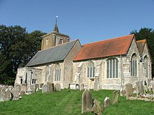 A stone church seen from the southeast. Nearest is the chancel with a red tiled roof, beyond that is the larger nave, with a slate roof, and at the west end is a tower with a spirelet