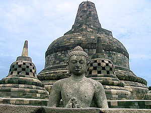 Candi of Indonesia - Buddha in an open stupa and the main stupa of Borobudur in the background.