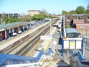 Sunbury (Surrey) railway station - Left: Sunbury railway station, car park, apartments and BT workshop. Right: Information board, passenger shelter and 1960s cuboid, tile-hung semi-detached houses.