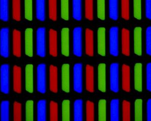 "LCD television - A close-up (300×) view of a typical LCD, clearly showing the sub-pixel structure. The ""notch"" at the lower left of each sub-pixel is the thin-film transistor. The associated capacitors and addressing lines are located around the shutter, in the dark areas."