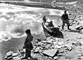 To personer og en liten båt ved elvebredden i Kautokeino 1956 - Norsk folkemuseum - NF.05535-180.jpg