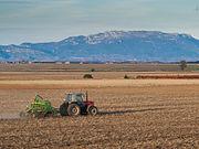Sebuah traktor yang sedang membajak lahan di La Rioja, Spanyol