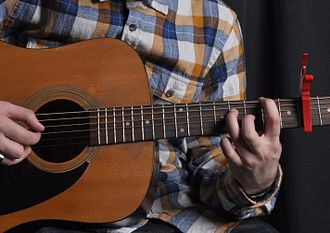 Capo - A guitar being played with a spring clamp capo