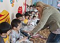 U.S. Air Force Master Sgt. Kirsten Smith, a dental technician with the 376th Expeditionary Medical Group, uses oversized props to demonstrate proper teeth brushing techniques to kindergartners in Bishkek 130319-F-KZ210-021.jpg
