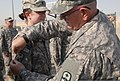 U.S. Army Sgt. Maj. Joseph E. Miracle, right, the support operations sergeant major for the 371st Sustainment Brigade, Ohio Army National Guard places the combat patch on Spc. Alexandra K Turowski, during 130701-Z-HY046-005.jpg