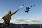 U.S. Navy Boatswain's Mate 2nd Class Cassandra Collier signals to a French Army SA 380 Puma helicopter as it takes off from the amphibious dock landing ship USS Pearl Harbor (LSD 52) while underway in 130628-N-WD757-242.jpg