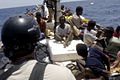 U.S. Navy and Marine Corps visit, board, search and seizure team members stationed aboard the guided missile cruiser USS San Jacinto (CG 56) stand guard over suspected pirates on board a dhow as they travel 100527-N-EF447-220.jpg