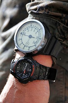 A diver's left wrist, wearing a diving watch and mechanical depth gauge with a needle indicator