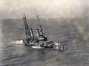 A sinking stripped battleship seen from a birds eyes view