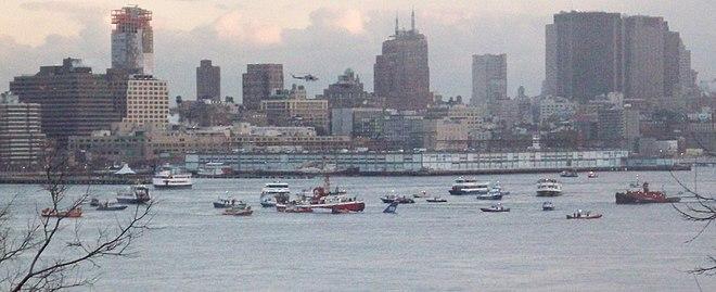 Photo montrant de nombreux navires au milieu du fleuve Hudson, près de l'avion, situé au centre de l'image, et dont seule sa queue est visible, le reste se trouvant sous l'eau. En arrière-plan se trouve la ville de New York.