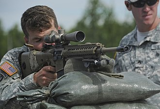 United States Army Sniper School - An instructor observes a student at M110 SASS qualifications during the Sniper Course's Mobile Training Team (MTT) event in Alaska (circa 2013)