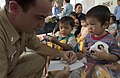 US Navy 060703-N-9851B-006 Ensign James Zumwalt, assigned to the rescue and salvage ship USS Salvor (ARS 52), uses a crayon to make a drawing for a child living in Thien Binh Orphanage.jpg