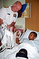 US Navy 070605-N-5827C-020 Director, Warfare Integration, Rear Adm. Kenneth Deutsch, points out planes that adorn a Navy squadron T-shirt for a young boy during a Caps for Kids visit at the University of Chicago Comer Children.jpg