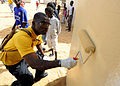 US Navy 100409-N-7948C-059 Hospital Corpsman 3rd Class Guy Leppry paints the outside walls of a classroom at Pikine17A and HLM grade school during a community outreach project in Pikine.jpg