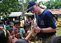 US Navy 110701-N-XR557-175 Musician 2nd Class Anthony Smouse interacts with children at Santa Lourdes Elementary School while playing his french ho.jpg