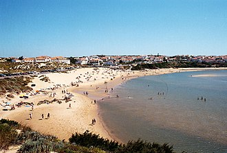 Vila Nova de Milfontes - The coastal beach with the main centre of Vila Nova de Milfontes in the background