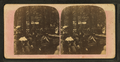 View of people standing and sitting at long tables under trees, by C. A. Sweetser & Co..png
