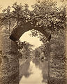 View though the central arch of a bridge over a canal, Sonargaon 1870.jpg
