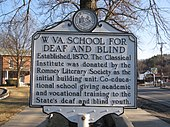A white historical marker with black lettering illustrating the history of the West Virginia Schools for the Deaf and Blind