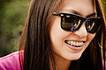 Woman with sunglasses, long hair, and braces.jpg