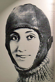 A sepia-tinged black-and-white photograph showing the head of a smiling woman. All but her face is under a leathery covering