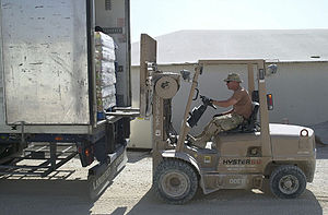 Airmain unloading a truck with forklift.