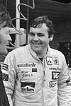 Alan Jones in a racing outfit smiling at another man