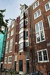 foto van Pand, bestaande uit een middendeel met pakhuisdeuren en twee zijstukken met vensters