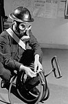An ARP Warden wearing a gas mask tidies the hose of his stirrup pump at an ARP post in Britain during the Second World War. D3892.jpg