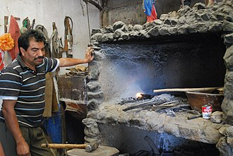Blacksmith - Traditional blacksmith next to his forge of stone and brick