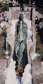 Bronze sculpture of a young woman reclining with legs crossed, surrounded by flowing water in the middle of a rectangular fountain