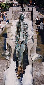Figuro de juna virino sidanta sur deklivo kun gamboj krucis. Ĝi estas en la mezo de rektangula fontano, ĉirkaŭita de torenta akvo.