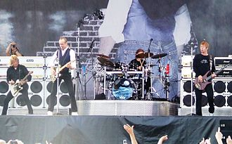 "Status Quo (band) - Performing at Arrow Rock Festival in Lichtenvoorde, the Netherlands in 2006; left-to-right: Rick Parfitt, Francis Rossi, Matt Letley (obscured by drums), John ""Rhino"" Edwards (out-of-shot: Andy Bown)"