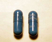 Two dark blue capsules with writing on them
