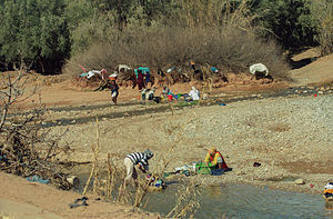 Water supply and sanitation in Morocco - In rural areas women wash clothes, as shown here on the Dades River. With increasing access to tap water and standpipes this practice has become less common