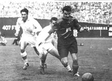 "A black-and-white photograph taken in the midst of a soccer match. A dark-haired player in a dark uniform marked ""ASL"" runs towards an old-fashioned leather ball in the foreground. Behind him two players in light-coloured kits can be seen."
